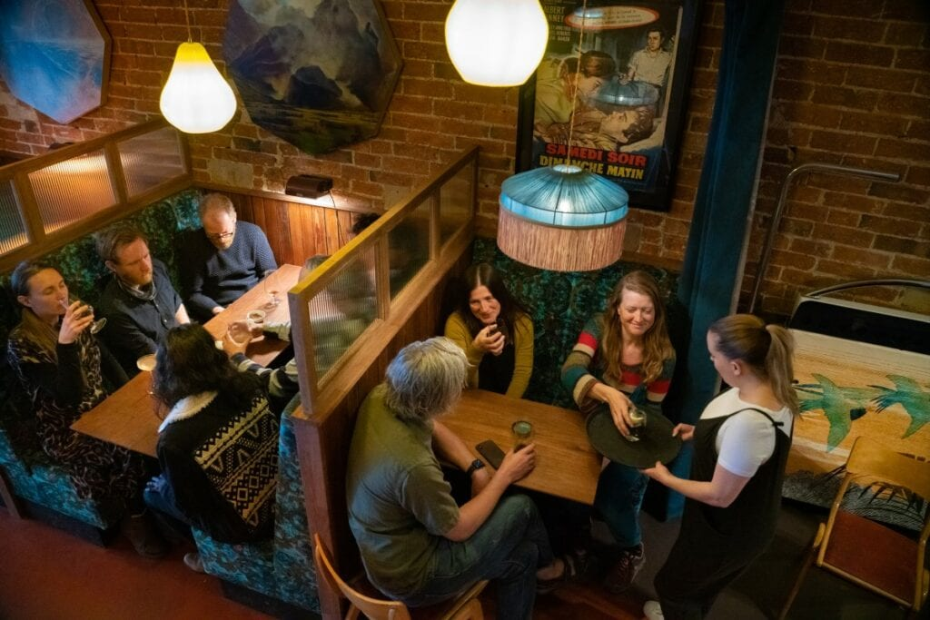 Two groups of people sat laughing and drinking in booths in the Northern Light Cinema bar area